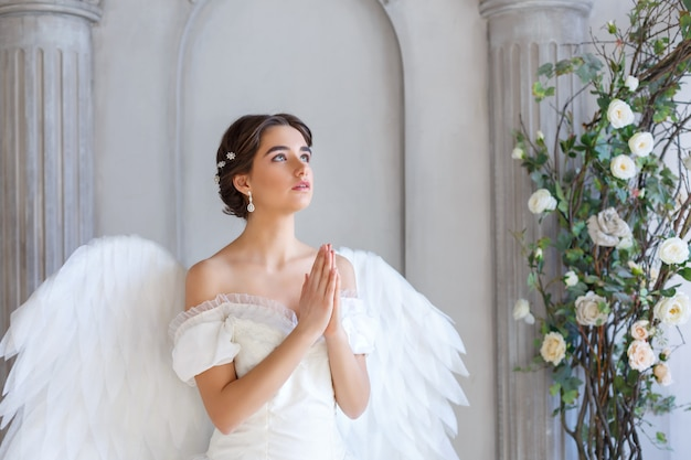Portrait of a beautiful young woman in a white dress and angel wings, standing with a pleading look against the background of a wall with columns and flowers