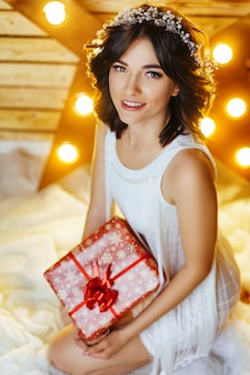 Portrait of a beautiful young woman who holds a gift for new year and christmas.