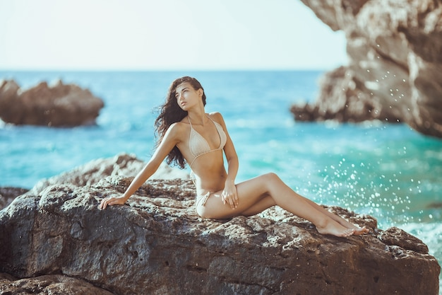 Portrait of beautiful young woman on wild rocky beach.