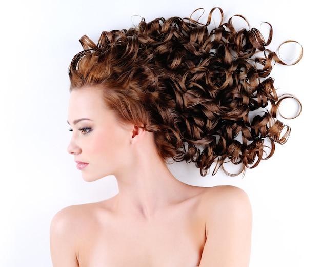 Ritratto di giovane e bella donna con i capelli lunghi riccioli di bellezza sdraiato sul pavimento