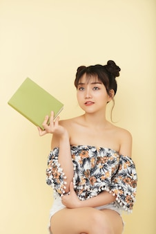 Portrait of beautiful young woman with book thinking about novel she read