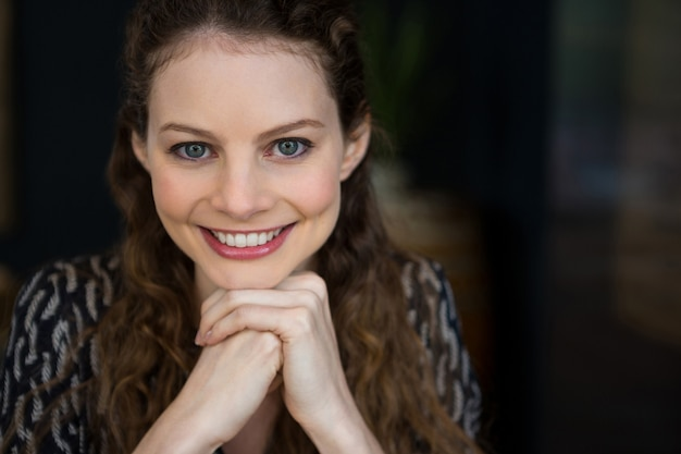 Portrait of beautiful young woman with brown hair in coffee shop