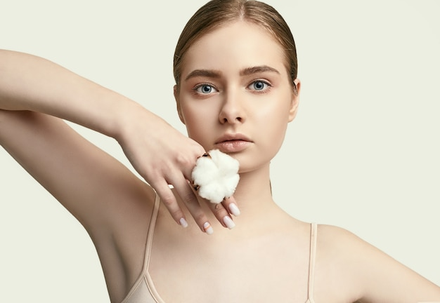 Portrait of beautiful young woman with clean perfect skin posing