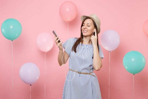 Portrait of beautiful young woman with closed eyes in straw summer hat blue dress with mobile phone and earphones listening music on pink background with colorful air balloons. birthday holiday party.