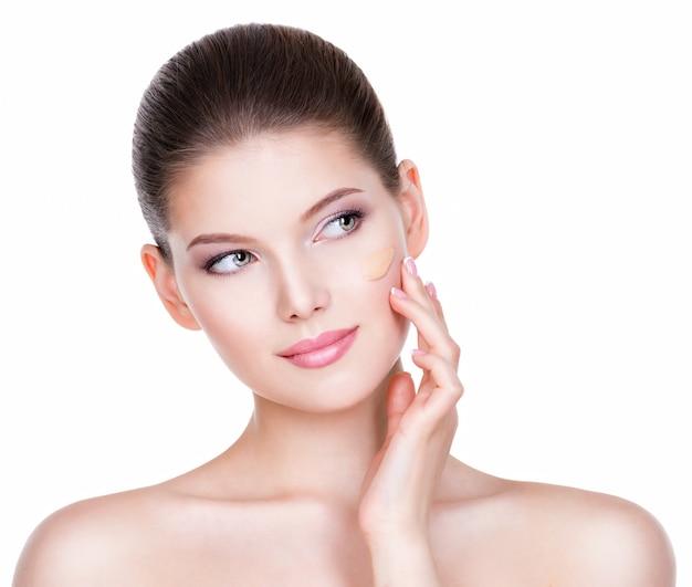 Ritratto di giovane e bella donna con fondotinta cosmetico su una pelle - isolato su sfondo bianco.