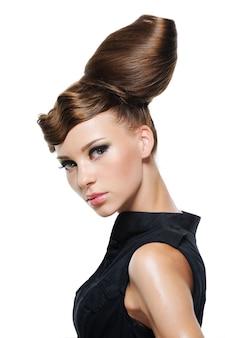 Ritratto di bella giovane donna con l'acconciatura di moda creativa