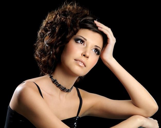 Ritratto di bella giovane donna con acconciatura creativa e trucco luminoso di moda