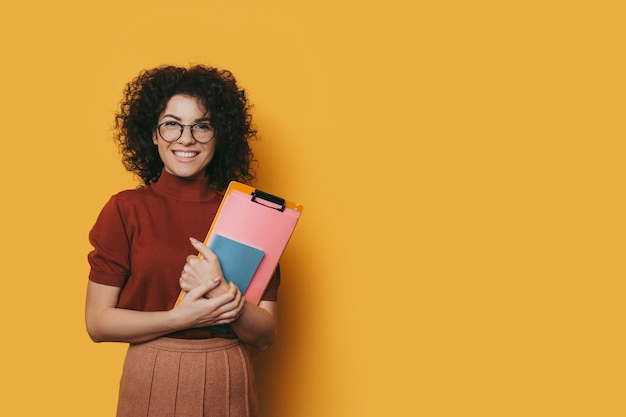 Portrait of a beautiful young woman with curly hair wearing glasses looking at camera laughing while holding her studying books isolated on yellow studio wall.
