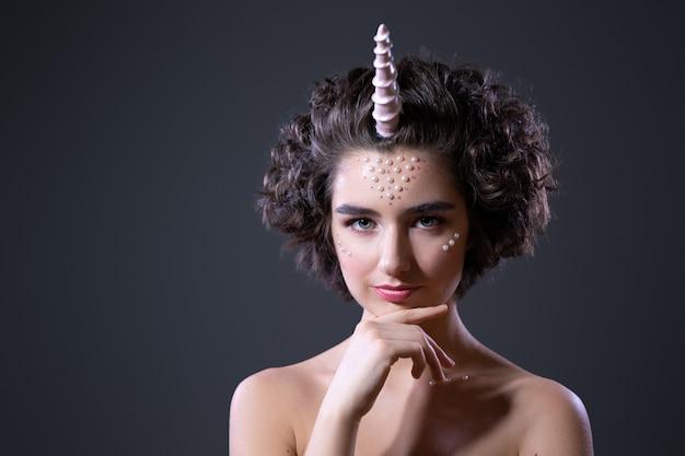 肖像画ビーズと彼女の顔に接着したビーズ、素晴らしいユニコーンの巻き毛の美しい若い女性。暗い背景に