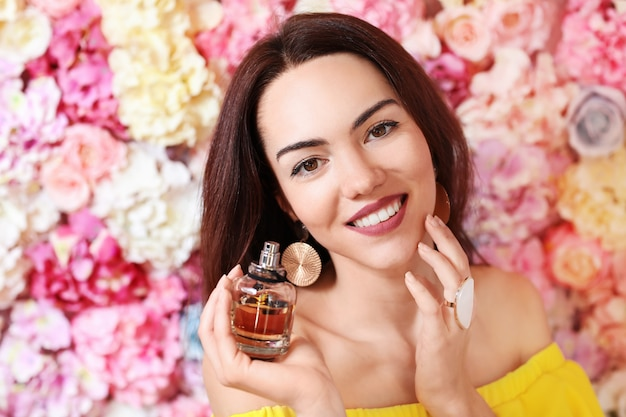 Portrait of beautiful young woman with floral perfume