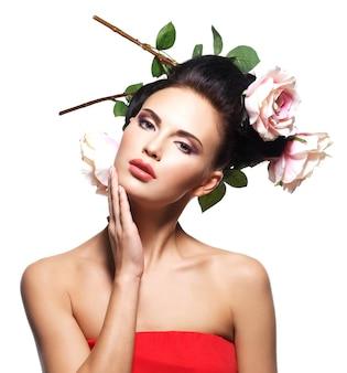 Ritratto di giovane e bella donna con fiori nei capelli, toccando il suo viso - isolato su bianco