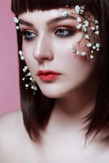 Portrait of beautiful young woman with flowers on her face. korean style makeup, doll beauty
