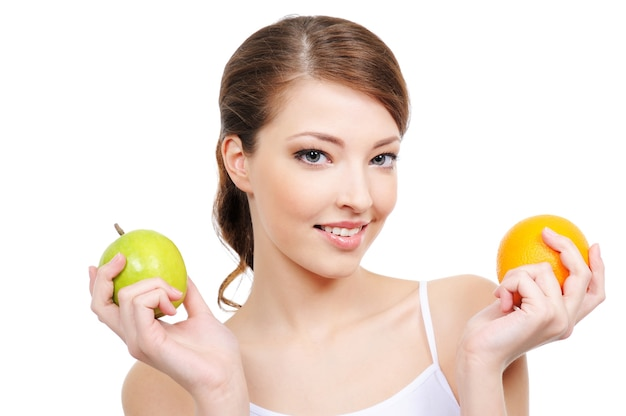 Ritratto di bella giovane donna con frutti isolati su bianco