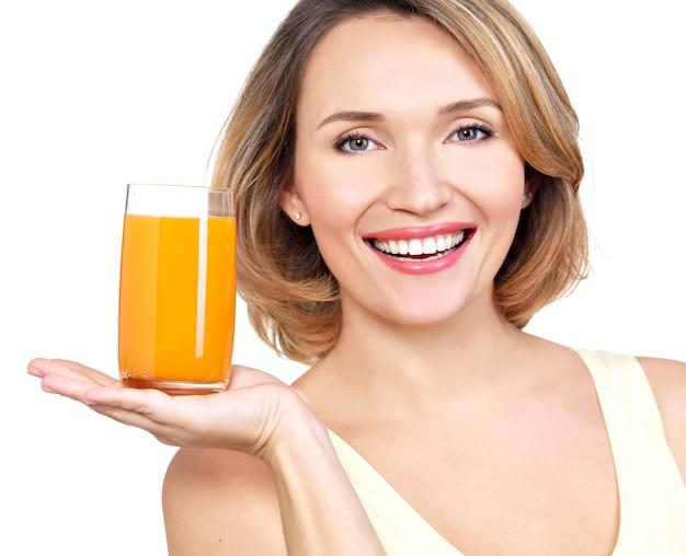 Ritratto di una giovane e bella donna con un bicchiere di succo isolato su bianco.