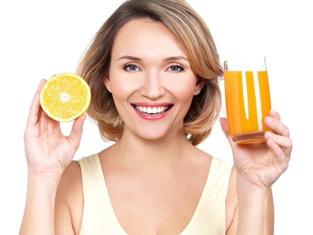 Ritratto di una giovane e bella donna con un bicchiere di succo di frutta e arancia isolato su bianco.
