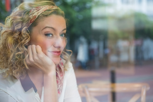 Portrait of beautiful young woman with hand on chin in coffee shop seen through window