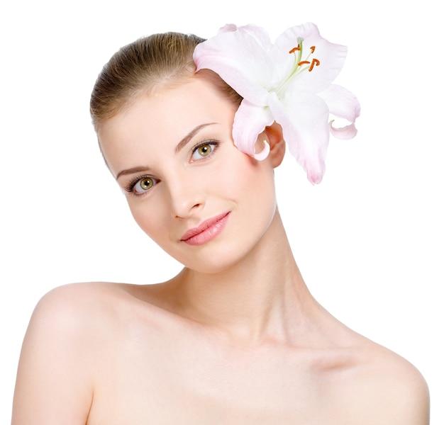 Ritratto di bella giovane donna con il giglio nei capelli - isolato su bianco