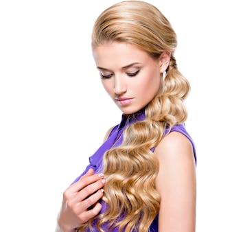Ritratto di bella giovane donna con capelli ricci biondi lunghi che osserva giù - isolato sulla parete bianca.
