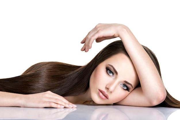 Ritratto di giovane e bella donna con lunghi capelli lisci castani isolati su bianco