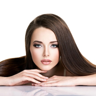 Portrait of beautiful young woman with long straight brown hair isolated on white Free Photo