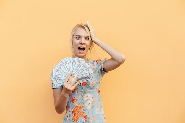 オレンジ色のパステル調の孤立した背景にお金と現金で美しい若い女性の肖像画