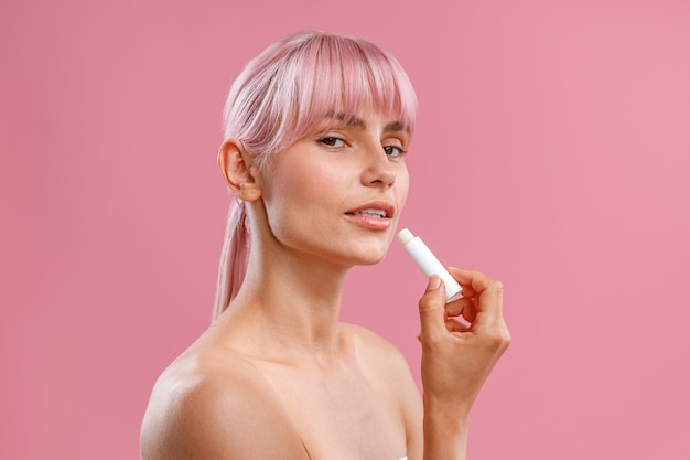 Portrait of beautiful young woman with naked shoulders holding lip balm near her lips isolated over