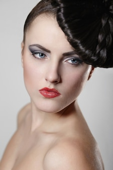 Portrait of beautiful young woman with red lips and unusual hair style on gray
