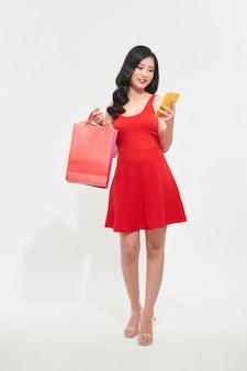 Портрет красивой молодой женщины с хозяйственными сумками и глядя на мобильный телефон