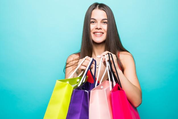 Ritratto di giovane e bella donna con borse della spesa sulla parete blu