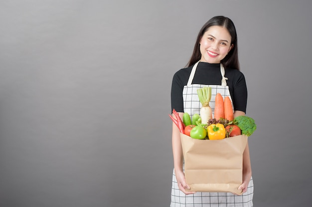 Portrait of beautiful young woman with vegetables in grocery bag in studio grey background