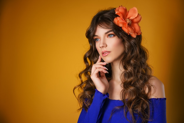 Portrait of a beautiful young woman on a yellow background