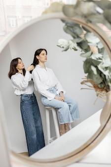 Portrait beautiful young women looking in mirror