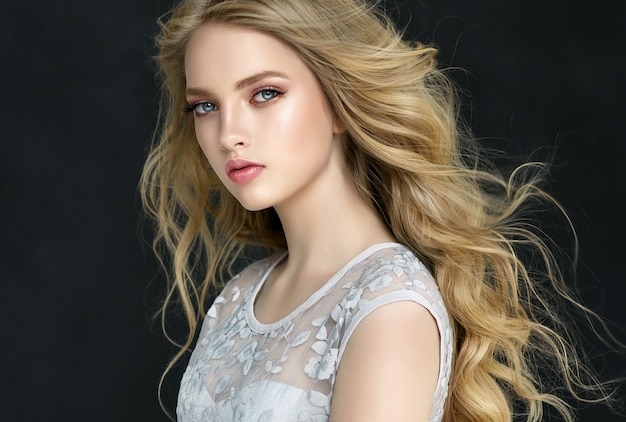 Portrait of beautifully looking young blonde haired woman dressed in a bright makeup.