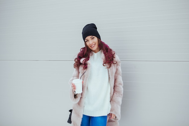 Portrait of beauty fashion smiling woman with coffee in mink coat and black hat . copy-space. colored hairs