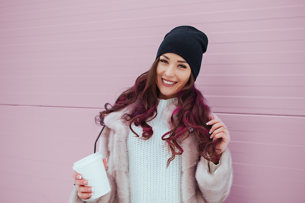 Portrait of beauty fashion smiling woman with coffee in mink coat and black hat . outdoor
