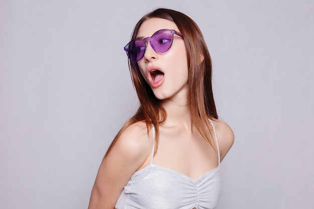 Portrait of beauty girl in eyeglasses white background. close up portrait of young cheerful beautiful girl with dark long hair smiling with teeth, looking in camera girl is surprised