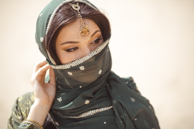 Portrait of beauty indian model with bright make-up who hiding her face behind the veil standing over gold desert background.