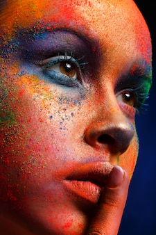Portrait of beauty model with colorful powder make up show hush sign. beautiful woman with creative splash makeup. abstract colourful art make-up, crop