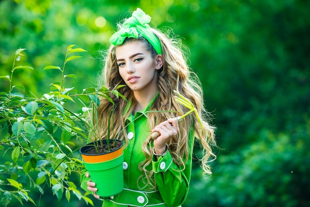 Portrait of beauty woman while working in garden beauty spring girl with flower pot springtime