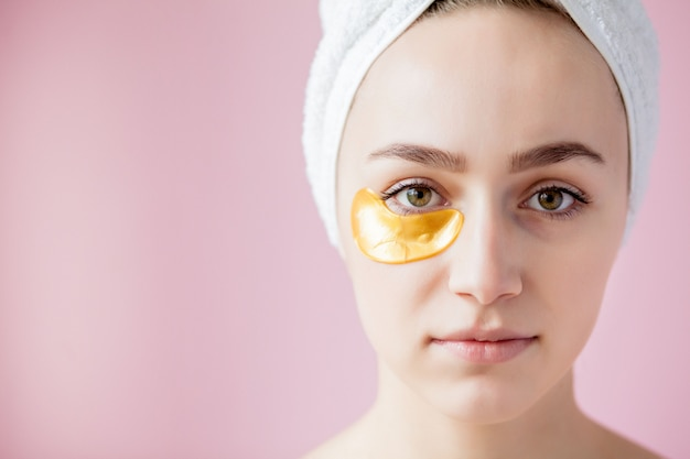 Portrait of beauty woman with eye patches on pink background.
