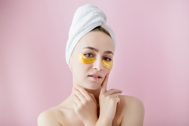 Portrait of beauty woman with eye patches on pink wall. woman beauty face with mask under eyes. beautiful female with natural makeup and gold cosmetics collagen patches on fresh facial skin.