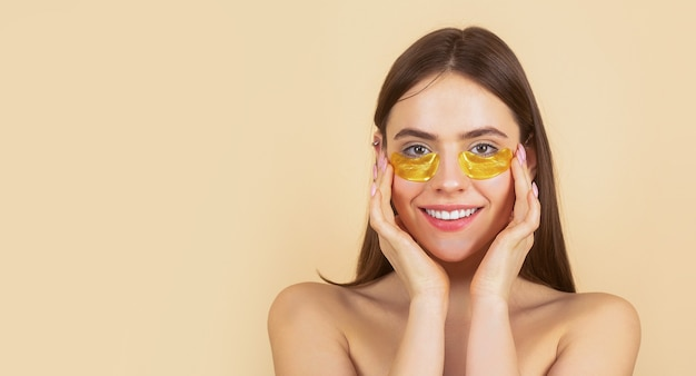 Portrait of beauty woman with eye patches showing an effect of perfect skin. brunette spa girl.