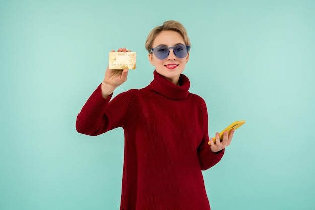 Portrait of beauty young girl in sunglasses showing plastic credit card while holding mobile phone isolated over blue background
