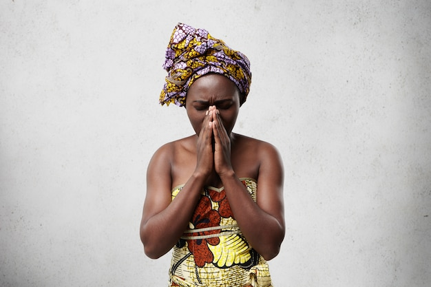 Portrait of begging black woman in traditional clothes pressing her palms together closing her eyes imploring for good luck of her children. religious african housewife praying for wellness of family