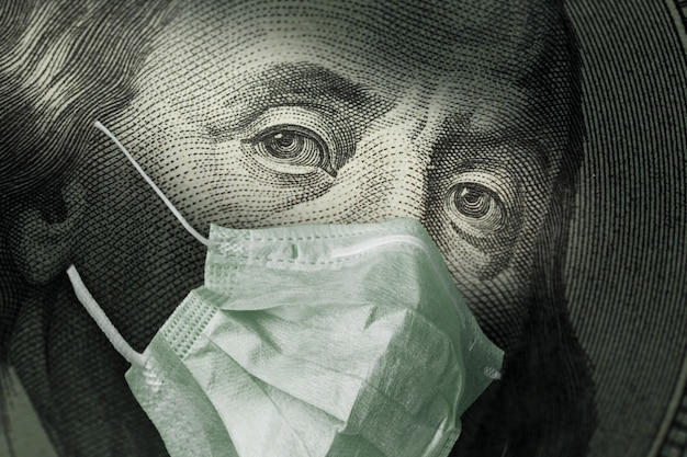 Portrait of benjamin franklin 100 dollar bills with a medical mask from the coronavirus covid-19.