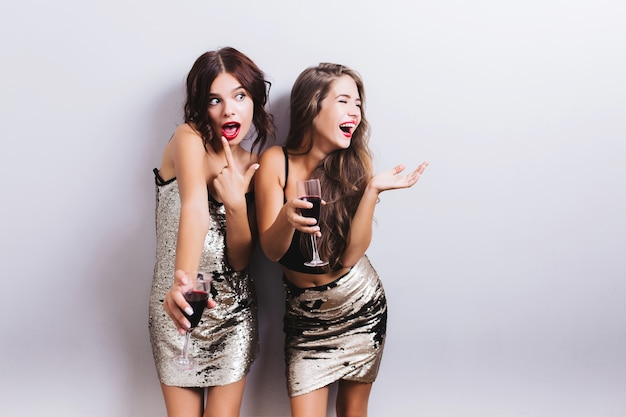 Portrait of best friends, pretty girls having fun, indoor party and drinking red wine, crazy looking, laughing. wearing trendy shiny dresses, skirt, have wavy hairstyle. isolated.