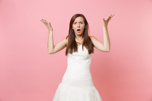 Portrait of bewildered shocked woman in beautiful white dress standing and spreading hands