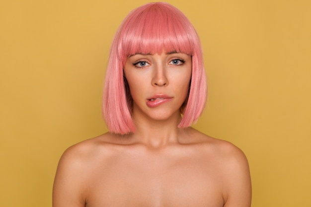 Portrait of bewildered young attractive woman with short pink bob haircut looking worringly at camera and biting underlip while standing against mustard wall