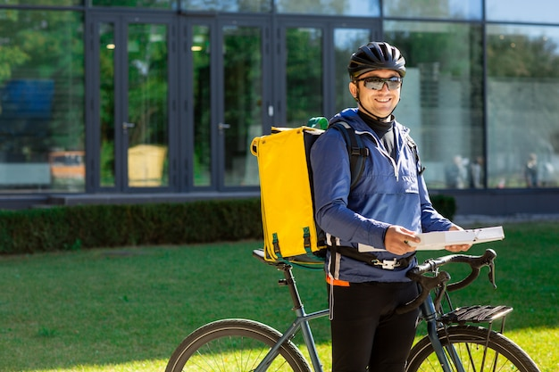 Portrait of bicycle courier with yellow bag and bike