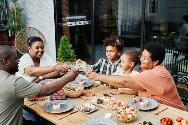 Portrait of big africanamerican family clinking glasses while enjoying dinner together outdoors and ...